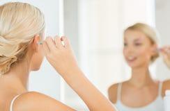 妇女有棉花棒的清洁耳朵在卫生间 库存照片