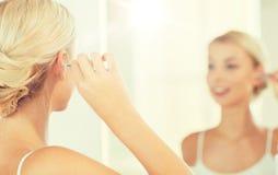 妇女有棉花棒的清洁耳朵在卫生间 库存图片