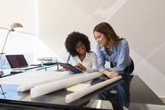 妇女有片剂个人计算机和图纸的同事建筑师 库存照片