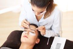 妇女有睫毛引伸在专业美容院 免版税库存图片