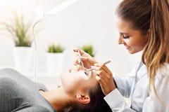 妇女有睫毛引伸在专业美容院 库存照片