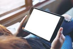 妇女有空白的白色屏幕的发怒有腿和举行的黑片剂个人计算机坐在咖啡馆的大腿 免版税库存图片