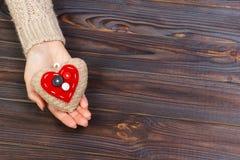 妇女有美好的准确被编织的红色心脏的` s手 在木背景的白色舒适被编织的毛线衣 给帮助的概念 库存照片