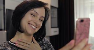 妇女有视频聊天使用享受聊天的智能手机对朋友 图库摄影