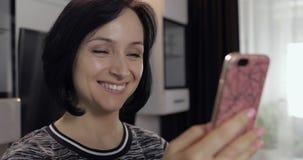 妇女有视频聊天使用享受聊天的智能手机对朋友 库存图片
