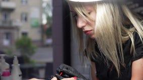 妇女有钉子修指甲在美容院有应用与涂药器的特写镜头观点的美容师油漆 影视素材
