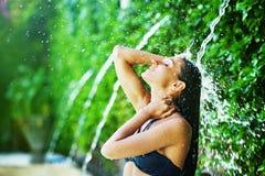 妇女有阵雨在热带瀑布下 免版税库存图片