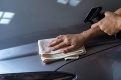 妇女有microfiber布料和干净的浪花的清洁汽车 免版税库存照片