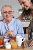 妇女服务早餐 免版税库存图片