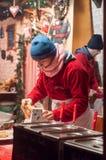 妇女服务churros在圣诞节市场上 库存图片