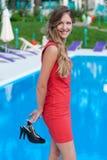 妇女松弛最近的游泳池 免版税库存照片