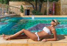 妇女松弛最近的游泳池 免版税图库摄影