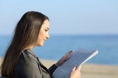 妇女松弛读书在海滩的一张报纸 免版税库存图片