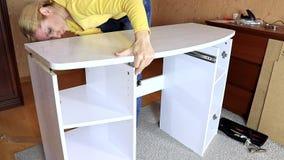 妇女架置新的白色家具,把桌面放的她在一个新的一半被装配的梳妆台上 影视素材