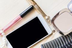 妇女染睫毛油 梳子和电话 免版税库存图片