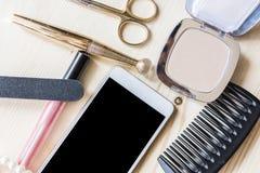 妇女染睫毛油 梳子和电话2 免版税库存照片