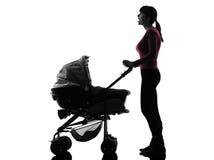 妇女查找惊奇的剪影的摇篮车婴孩 库存照片