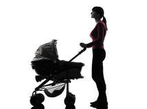 妇女查寻剪影的摇篮车婴孩 图库摄影