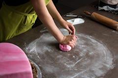 妇女桃红色方旦糖为装饰的蛋糕,手细节做准备 免版税库存照片