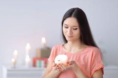 妇女梦想有一个装饰蜡烛的在客厅的被弄脏的背景 库存图片