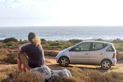 妇女梦想,当坐海滩在她的汽车旁边时 免版税库存图片