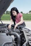 妇女检查一辆残破的汽车 免版税库存照片