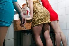 妇女检查他们组成在洗手间 免版税图库摄影