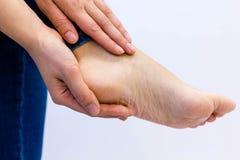 妇女检查她酸疼的脚 孕妇特写镜头递做脚按摩 toching一赤裸酸疼的起皱纹的手 免版税库存照片
