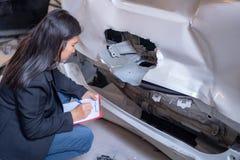 妇女检查汽车事故 免版税图库摄影