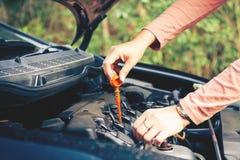 妇女检查汽车的机器润滑油 库存图片