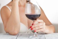 妇女检查红葡萄酒 免版税库存照片