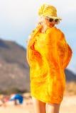 妇女橙色礼服海滩 免版税库存照片