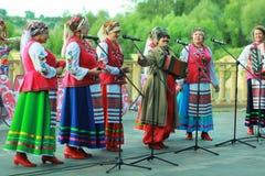 妇女歌手室外表现穿乌克兰种族传统衣裳和庆祝异教的假日伊冯Kupala的 免版税库存照片