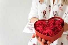 妇女正面图递拿着心脏与新鲜的玫瑰的箱子礼物 免版税库存图片