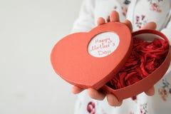 妇女正面图递拿着心脏与新ros的箱子礼物 免版税图库摄影
