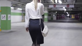 妇女步行后面看法与马尾、白色衬衫和黑裙子的在车库 影视素材