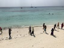 妇女步行在海滩桑给巴尔,坦桑尼亚-非洲 免版税图库摄影