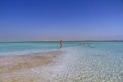 妇女步行在水死海 免版税库存图片