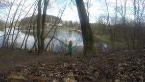 妇女步行通过森林公园道路 湖,房子,天空 4K 影视素材