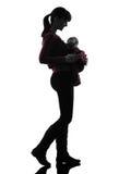 妇女母亲走的婴孩剪影 免版税库存照片