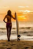 妇女比基尼泳装冲浪者&冲浪板日落海滩 免版税图库摄影
