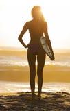 妇女比基尼泳装冲浪者&冲浪板日落海滩 库存照片
