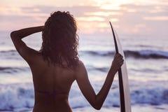 妇女比基尼泳装冲浪者&冲浪板日落海滩 免版税库存照片
