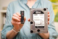 妇女比较NVE和硬盘驱动器硬盘驱动器 免版税库存图片