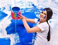 妇女油漆墙壁在家。 免版税库存照片