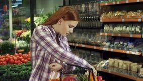 妇女注视着在她的购买大型超级市场 股票视频