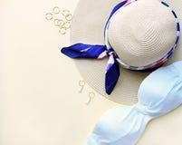 妇女泳装、帽子和fachion辅助部件的构成在biege背景,平的位置,顶视图 r 免版税库存照片