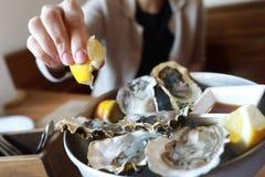 妇女洒牡蛎 免版税库存照片