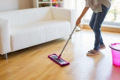 妇女洗涤的地板,房子保持 免版税库存照片