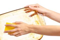 妇女洗着与厨房海绵的油腻肮脏的玻璃盘子 免版税库存图片